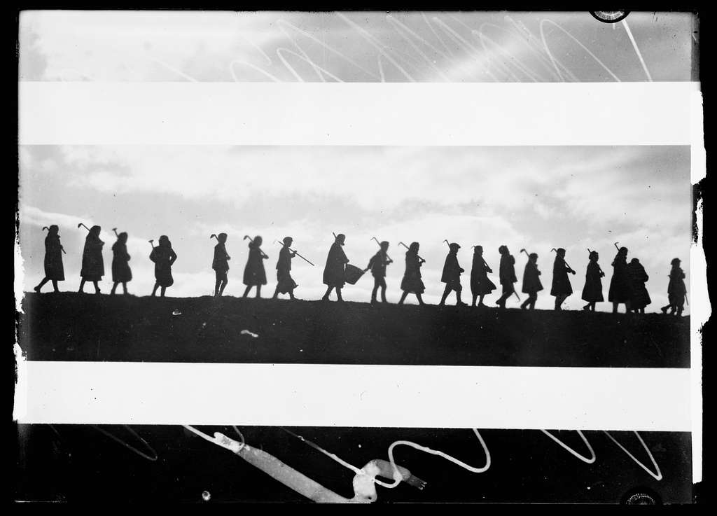Black and white photograph silhouette of group of figures in a line carrying tools.